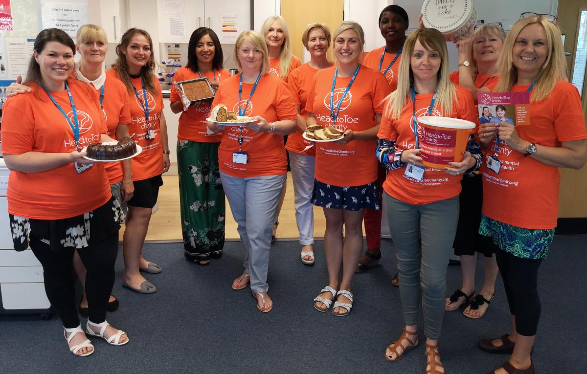 Group of women in Head to Toe charity shirts holding collection buckets and cakes